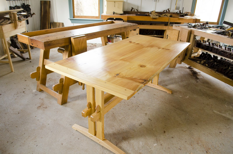 Finished trestle table sitting next to woodworking workbenches in Joshua Farnsworth's woodworking workshop