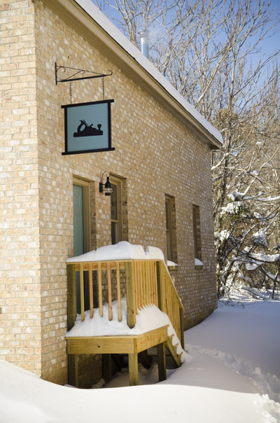 Wood And Shop Traditional Woodworking School brick building covered in a blanket of snow