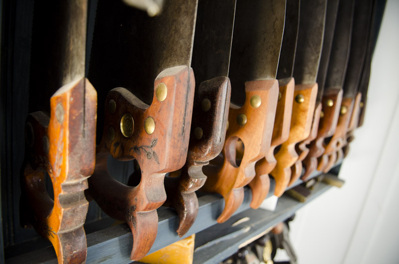 Antique hand saws lined up in a saw till in Joshua Farnsworth's Wood And Shop Traditional Woodworking School