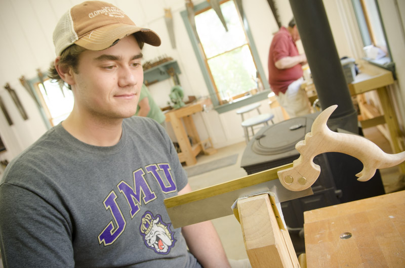 A JMU college student admiring his finished dovetail saw at Joshua Farnsworth's Wood And Shop Traditional Woodworking School
