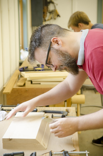 A bearded Woodworking student gluing up a donkey's ear shootinb board at the Wood and Shop Traditional Woodworking School