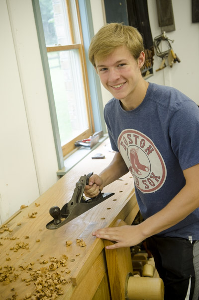 Young woodworking student using a stanley hand planer at the Wood and Shop Traditional Woodworking School