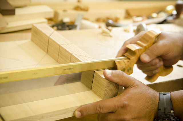 Woodworking student cutting a miter slot on a bench hook with a Lie-Nielsen dovetail saw
