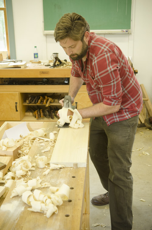 bearded male woodworking student using a stanley bailey No. 7 jointer plane to square a poplar board on a woodworking workbench at Joshua Farnsworth's Wood And Shop Woodworking School