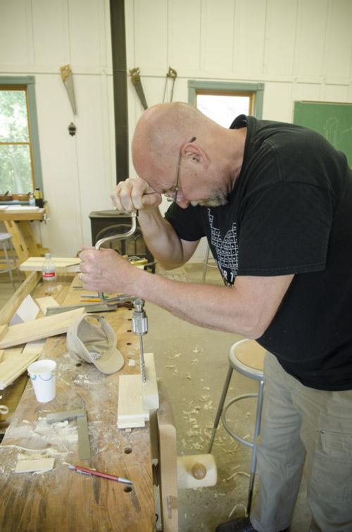 older gentleman woodworking student boring a hole using a brace and auger bit on a board at Joshua Farnsworth's Wood And Shop Woodworking School