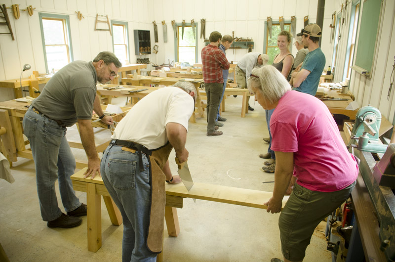 woodworking students using crosscut hand saws to cut poplar boards on saw horses at Joshua Farnsworth's Wood And Shop Woodworking School
