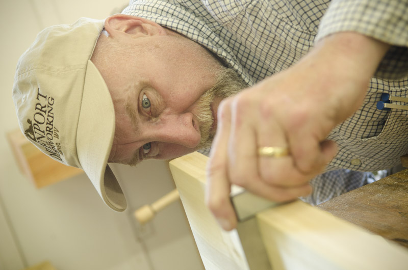 older gentleman woodworking student using a try square to check squareness on a board at Joshua Farnsworth's Wood And Shop Woodworking School