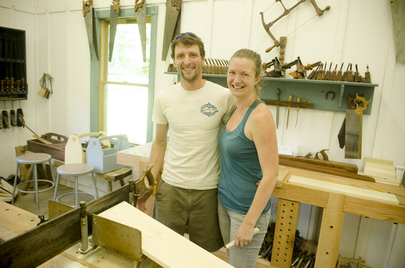 male & female woodworking students smiling near a woodworking workbench at Joshua Farnsworth's Wood And Shop Woodworking School