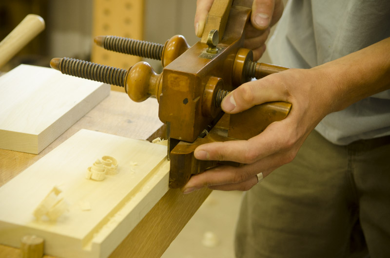 male woodworking using an antique boxwood plow plane to cut a groove on a woodworking workbench at Joshua Farnsworth's Wood And Shop Woodworking School