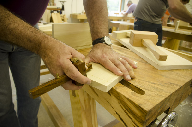 male woodworking laying out a dovetail joint with a marking gauge on a woodworking workbench at Joshua Farnsworth's Wood And Shop Woodworking School