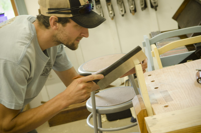 young male woodworking student cutting dovetails with a dovetail saw on a woodworking workbench at Joshua Farnsworth's Wood And Shop Woodworking School