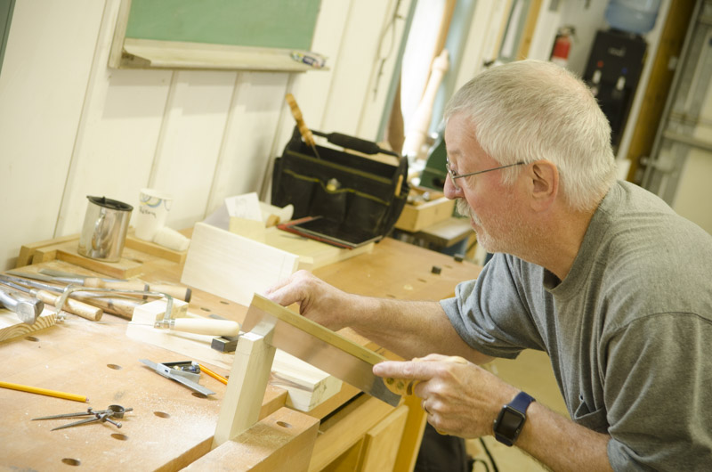 male woodworking student cutting dovetails with a dovetail saw on a woodworking workbench at Joshua Farnsworth's Wood And Shop Woodworking School