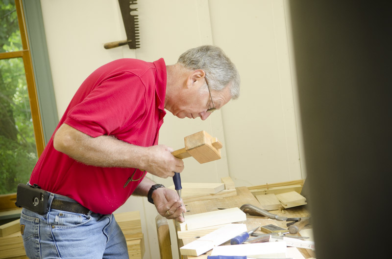 Make woodworking student cutting dovetails with joiner's mallet and chisel on a woodworking workbench at Joshua Farnsworth's Wood And Shop Woodworking School