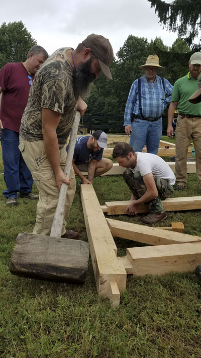 Woodworking Students measuring lumber at a timber framing or timber frame class at the wood and shop traditional woodworking school
