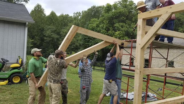 Woodworking Students raising roof beams at a timber framing or timber frame class at the wood and shop traditional woodworking school